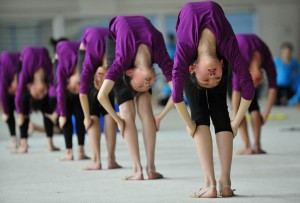 Students stretch during a training session at a gymnastic course at Shenyang Sports School in Shenyang